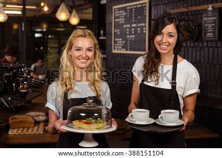 Pretty waitresses posing in front of the counter presenting coffee and pie at the coffee shop - stock photo