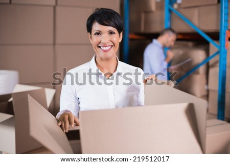 Pretty warehouse manager looking in box in a large warehouse