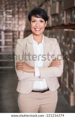 Pretty warehouse manager smiling at camera in a large warehouse