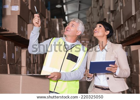 Pretty warehouse manager talking to foreman in a large warehouse - stock photo