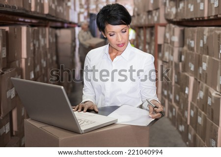 Pretty warehouse manager using laptop in a large warehouse - stock photo
