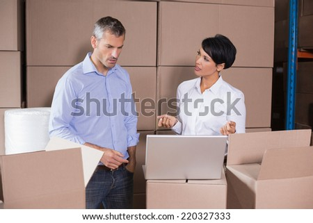 Pretty warehouse manager using laptop with colleague in a large warehouse