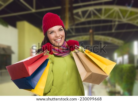 Pretty Warmly Dressed Mixed Race Woman In Outdoor Mall with Shopping Bags. - stock photo