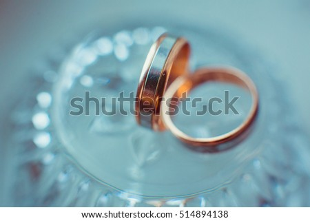 Pretty wedding rings lie on the crystal chest