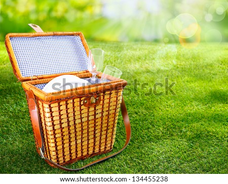 Pretty wicker picnic basket with a fresh blue and white lining standing open on a sunny green summer lawn to display plates and glasses - stock photo