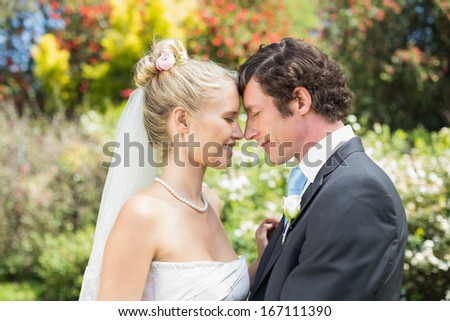 Pretty wife touching noses with new husband in the countryside