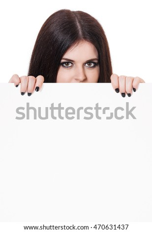 Pretty witch look out from behind of blank billboard over white background