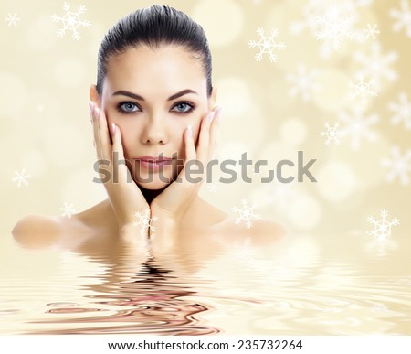 Pretty woman against an abstract background with snowflakes - stock photo