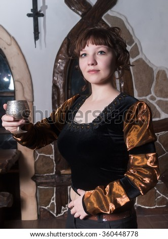 Pretty woman an armchair and with wine glass - stock photo