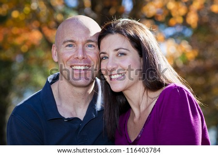 Pretty woman and husband fall portrait outdoors - stock photo