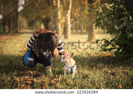 Pretty woman and little dog in the park - stock photo