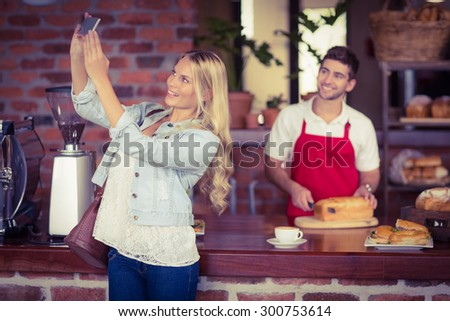 Pretty woman and waiter taking a selfie at the coffee shop