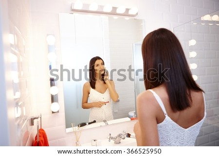 Pretty woman applying makeup in bathroom mirror.