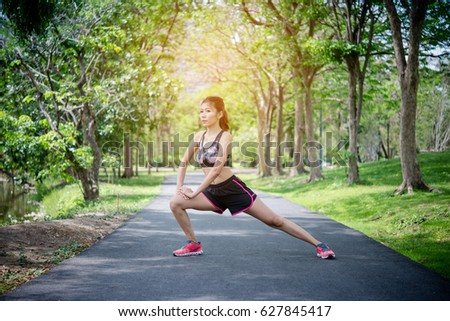 Pretty woman are exercising, Stretch the line in the park. Female runner resting after successful jogging exercise outdoors. Exercise concept.