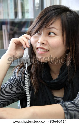 Pretty woman at work, using a phone - stock photo
