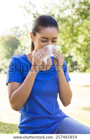 Pretty woman blowing her nose on a sunny day
