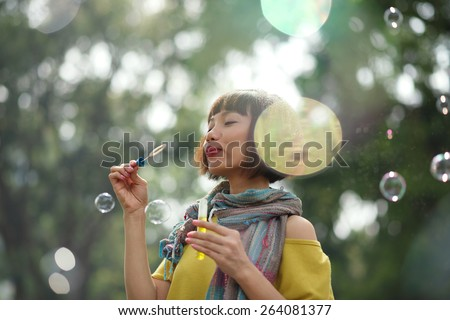 Pretty woman blowing soap bubbles in the park