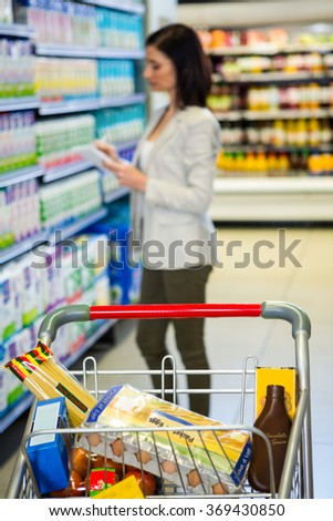 Pretty woman checking list in supermarket