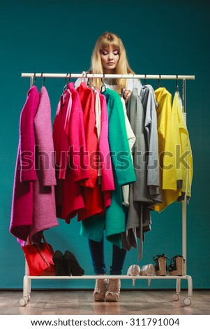 Pretty woman choosing clothes to wear in wardrobe. Attractive young girl customer shopping in mall shop. Fashion clothing sale concept. - stock photo
