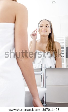 Pretty woman cleaning her face in the bathroom.