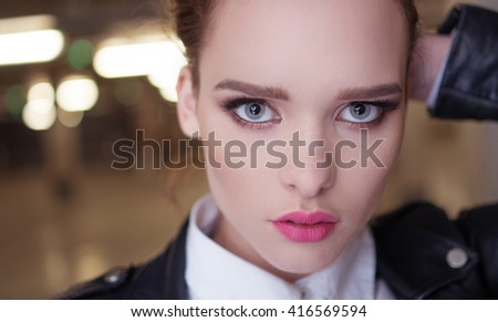 pretty woman close-up with blue eyes and full lips wearing leather jacket  - stock photo