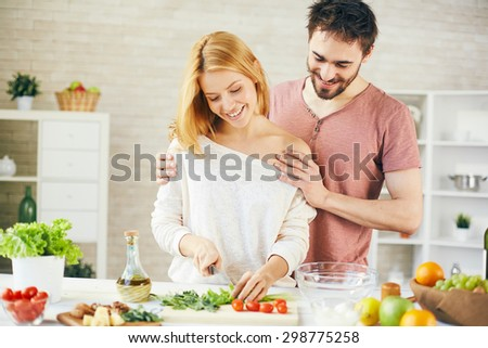 Pretty woman cutting lettuce for vegetable salad with her husband near by - stock photo