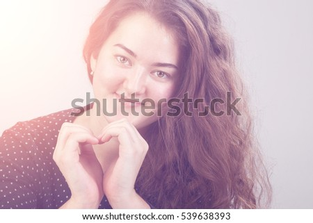 Pretty woman doing a heart with her hands. Toned