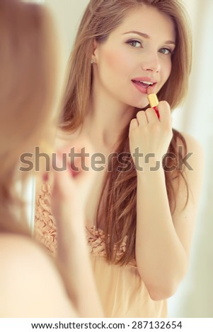 Pretty woman doing make up - stock photo
