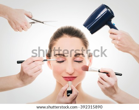 Pretty woman doing makeup with several beauty product  - stock photo