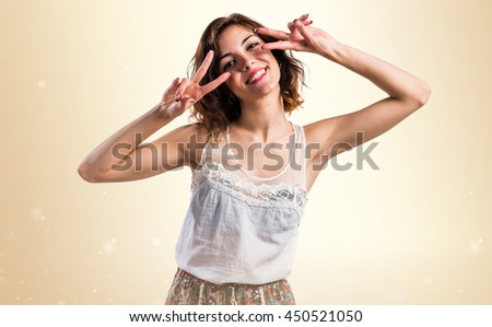 Pretty woman doing victory gesture over ocher background