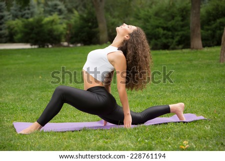 Pretty woman doing yoga exercises in outdoor park,  green grass background