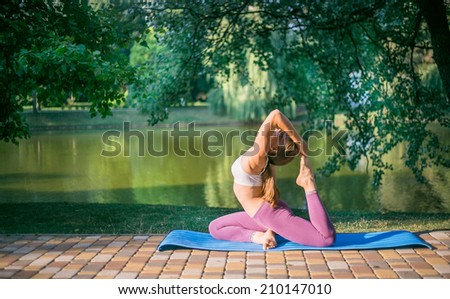 Pretty woman doing yoga exercises in the park near lake - stock photo