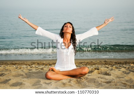 Pretty woman doing yoga on the beach - stock photo