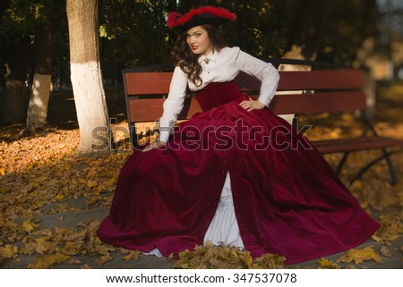 Pretty woman dressed in a retro-style on the autumn alley