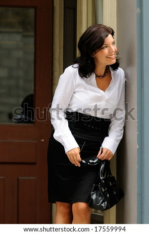Pretty Woman Dressed In Business Wear Looking Out From A Doorway - stock photo