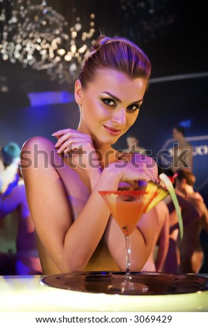 pretty woman drinking cocktail in nightclub, different kinds of lighting, shallow DOF - stock photo