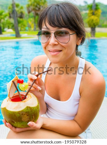 Pretty woman drinking coconut cocktail against outdoor pool - stock photo