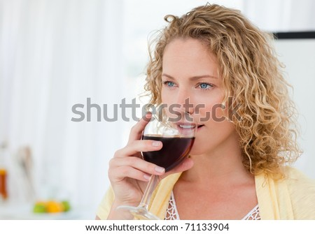 Pretty woman drinking some wine at home - stock photo