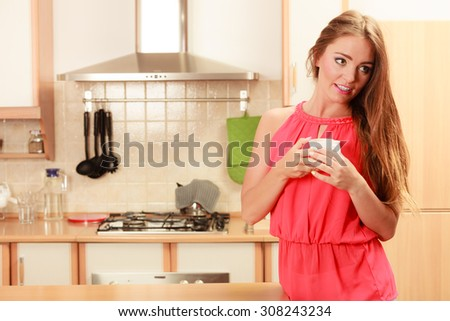 Pretty woman drinking tea or coffee at home. Gorgeous young girl with hot beverage relaxing in kitchen.