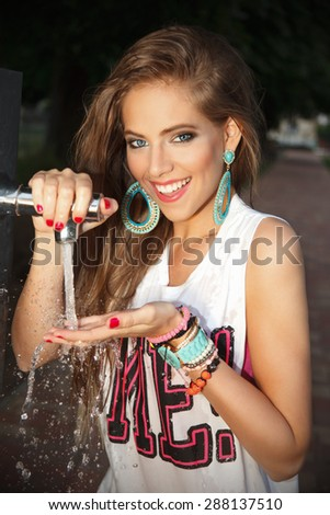 Pretty woman drinking water in the park - stock photo