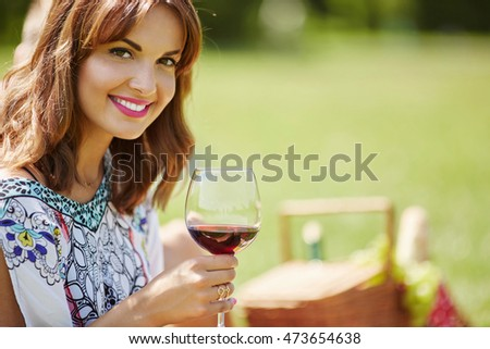 Pretty woman drinking wine on the picnic