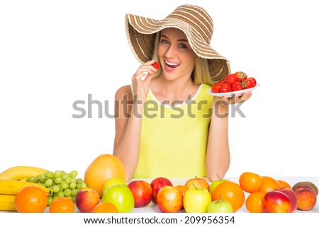Pretty woman eating a strawberry - stock photo