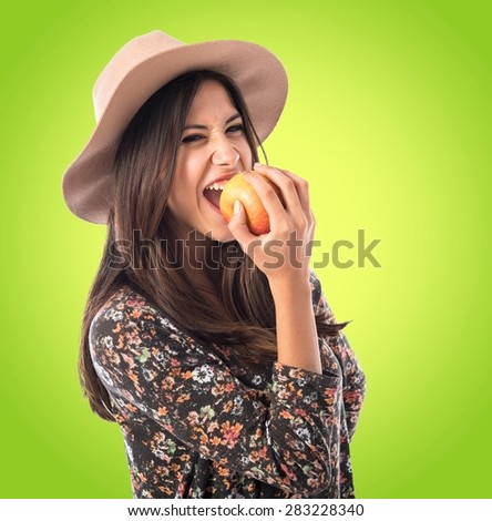 Pretty woman eating an apple over colorful background - stock photo