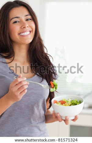 Pretty woman enjoying a bowl of salad while standing in the kitchen - stock photo