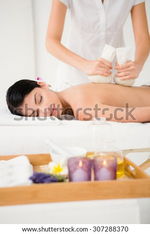 Pretty woman enjoying a herbal compress massage at the health spa - stock photo