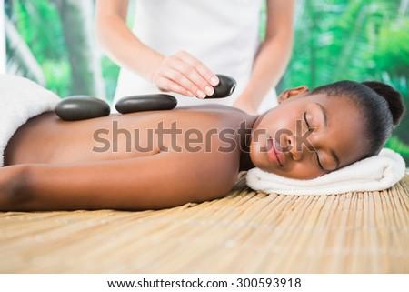 Pretty woman enjoying a hot stone massage at the health spa - stock photo