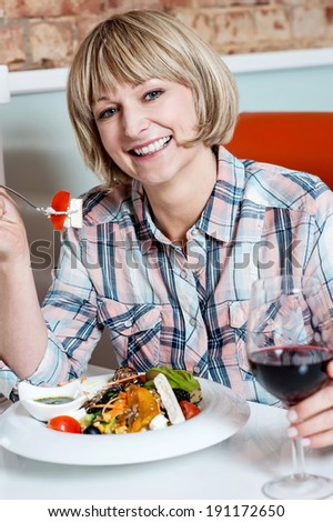 Pretty woman enjoying her meal in a restaurant - stock photo