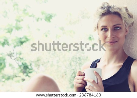 Pretty woman enjoying her morning coffee on a veranda