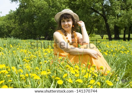 Pretty woman European brunetter in hat and orange dress sitting on green meadow with many yellow dandelions.