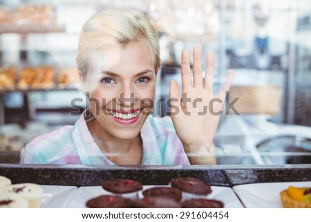 Pretty woman gesturing a greeting at the bakery - stock photo